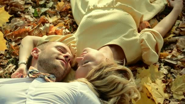 Smiling couple lying in autumn park