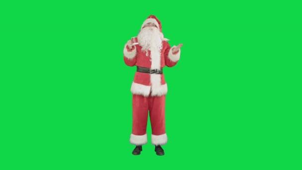 Santa Claus pití horkého čaje nebo kávy a přání Veselé Vánoce na zelené obrazovce, Chroma Key.
