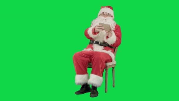 Santa Claus, sedí na židli s písmeny v rukou na klíč Chrome Green Screen