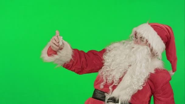 Santa Claus, hogy selfie, gazdaság egy nagy jelen egy zöld képernyő Chrome kulcs
