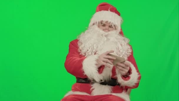 Santa mit Weihnachten Buchstaben oder Wunschliste auf einem Green-Screen-Chrom-Key