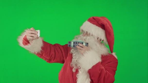 Holding egy selfie okostelefon-egy zöld képernyő Chrome kulcs csinál nagy ajándékot Santa Claus