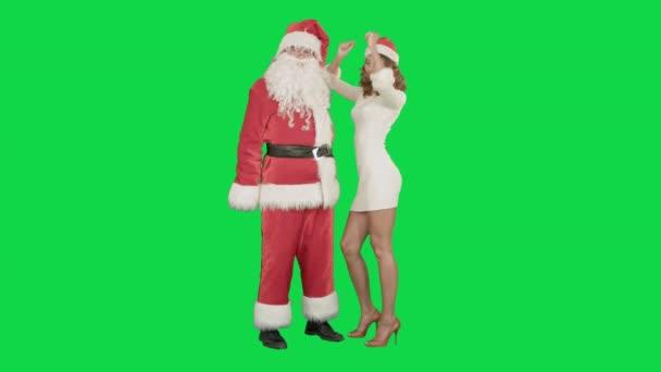 Vánoční šťastný úsměv dívka tančí s Santa Claus na klíč Chrome Green Screen
