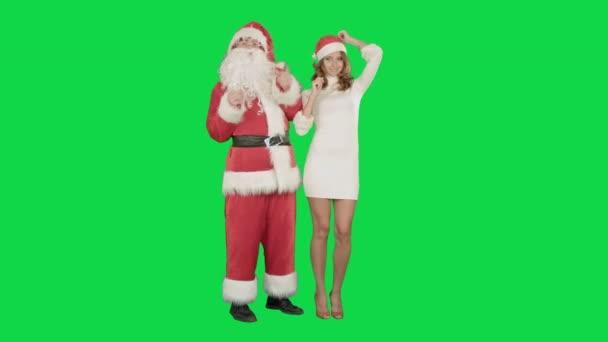 Santa Claus izgatott pinup táncoló nő egy zöld képernyő Chrome kulcs