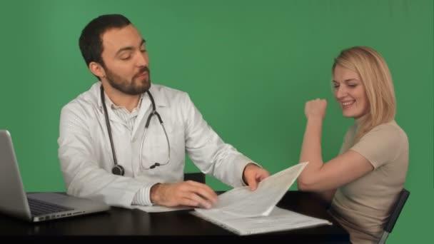 Lächelnder Arzt liest Krankengeschichte der jungen Frau im Krankenhaus auf grünem Bildschirm, Chroma-Schlüssel