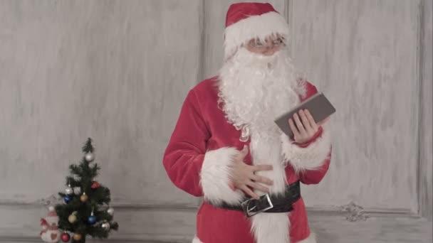 Santa Claus pomocí tabletového počítače na bílém pozadí