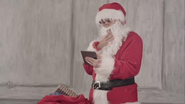 Santa claus s počítačem tablet pc kontrolu taštička.
