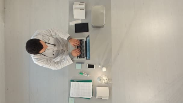 Top view of Male doctor write medical reports - at work use laptop