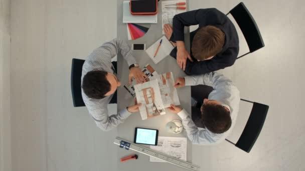 Pohled shora kolegy bytoví designéři pojednávající o data s prázdnou obrazovku nový moderní počítač notebook a pro digitální tablet s materiálem