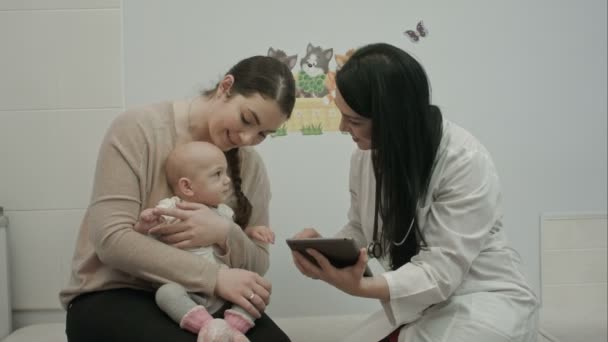 female doctor play with newborn baby and shows tablet  to mother