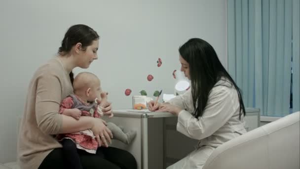 Pediatrician doctor at medical cabinet gives recommendations to mother with newborn twins