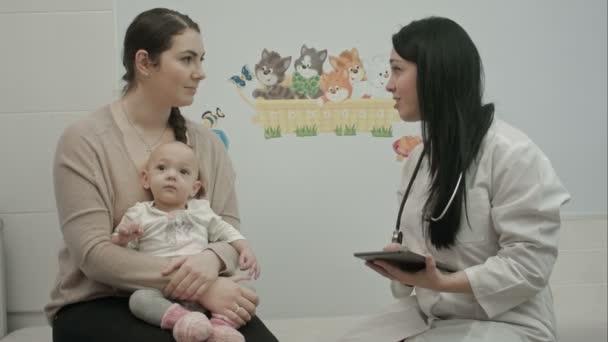 freundliche Kinderärztin erklärt Mutter mit Neugeborenem etwas