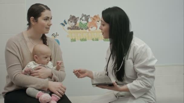 Kinderärztin zeigt Frau mit kleinem Baby etwas auf Tablet