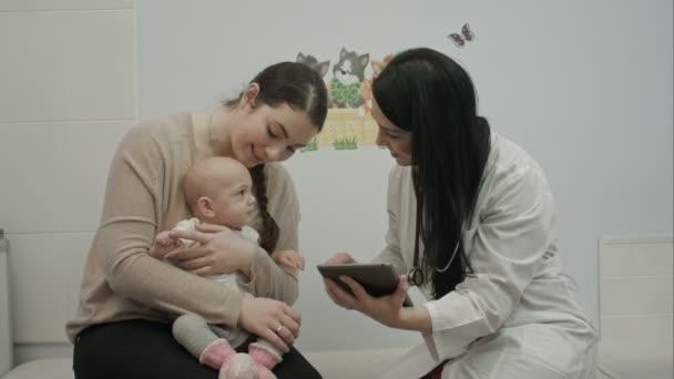 ženský lékař hrát s novorozeně a ukazuje tablet k matce