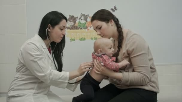 Childrens doctor listening to breathing newborn baby sitting in hands of mother