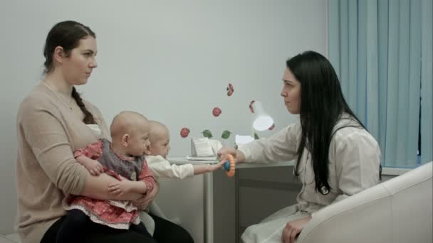 Female pediatrician doctor explain something to mother with newborn twins