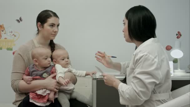 Female pediatrician doctors explaining something to mother with newborn twins and writing a prescription for drugs