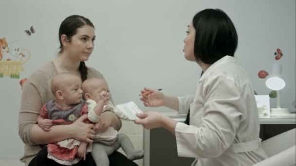 Weibliche Kinderärzte erklären Mutter mit neugeborenen Zwillingen etwas und schreiben ein Rezept für Medikamente