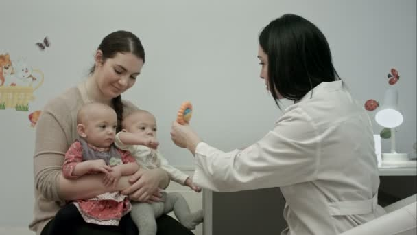 Cute newborn twins being examine by pediatrician with toy