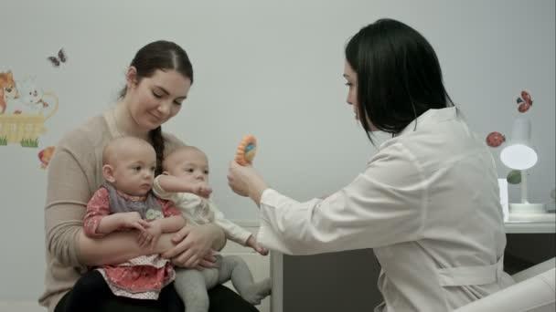 Niedliche neugeborene Zwillinge werden mit Spielzeug vom Kinderarzt untersucht