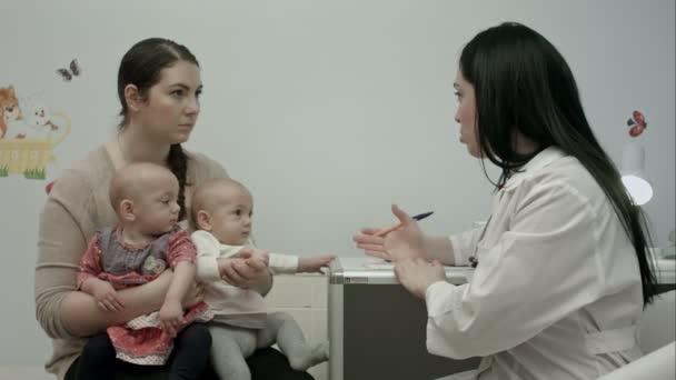 Kinderärztin erklärt Mutter mit neugeborenen Zwillingen in modernem Krankenhaus etwas