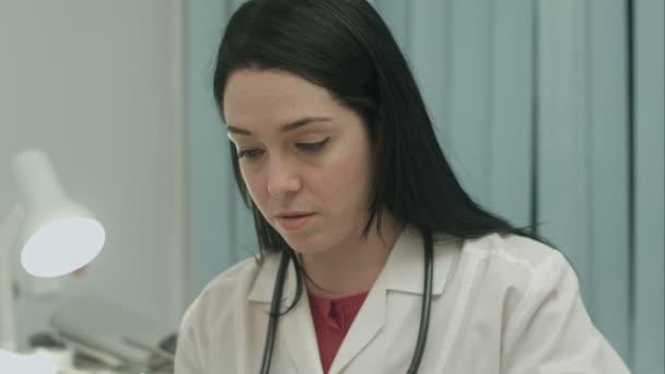 Ärztin in Arztpraxis analysiert Ergebnisse ein Elektrokardiogramm und nimmt Hinweise