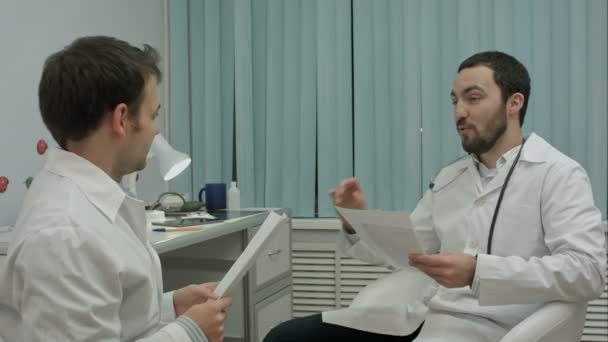 Bearded doctor shows new drugs to intern
