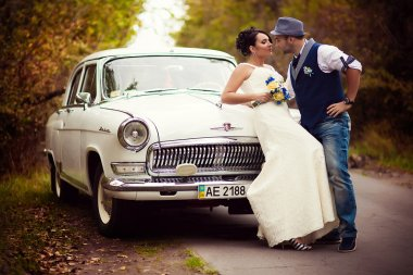 groom and bride near car