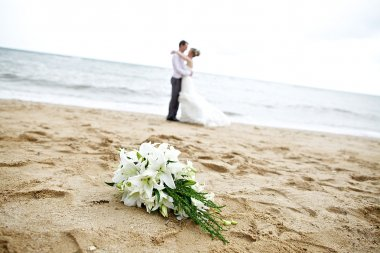 bueatiful wedding bouquet flower with couple on the beach