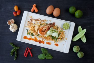pad thai, shrimp and vegetable on a plate with ingredients surrounding