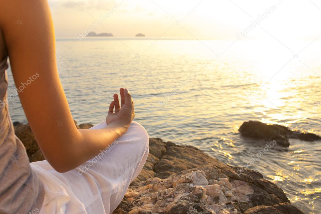 Young woman meditation yoga pose on the beach
