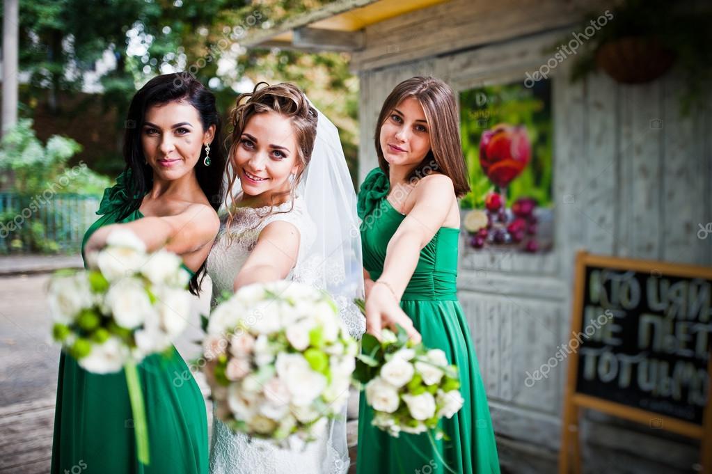 372607dc89d0 Thre okouzlující nevěstu a družičky ukazující svatební kytice na — Stock  fotografie