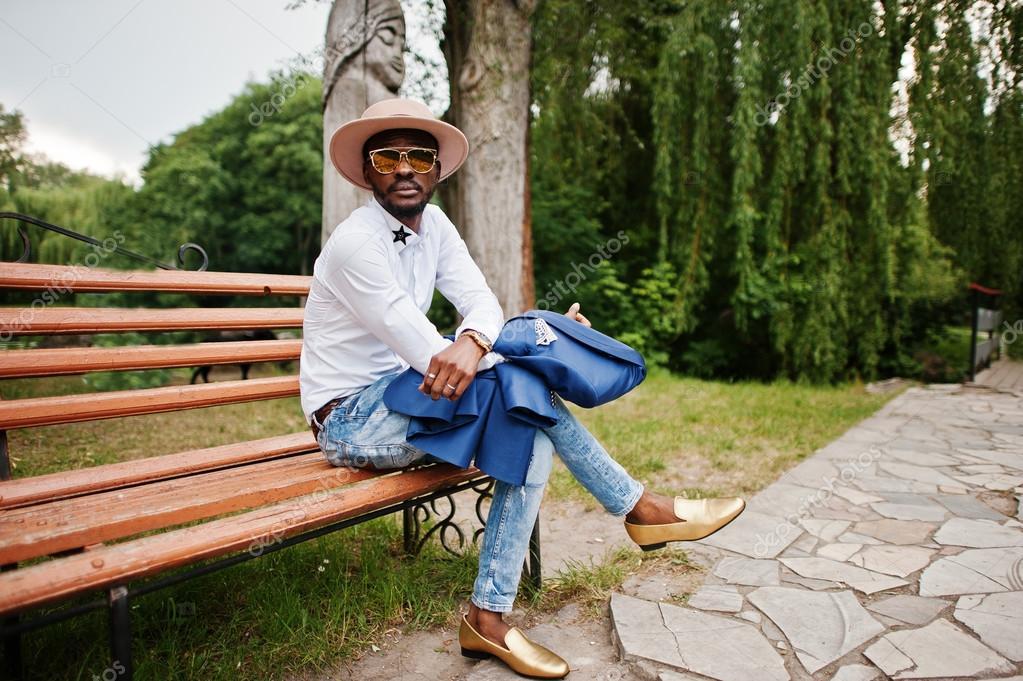 Багаті чорна людина сидить на лавці в сонцезахисні окуляри f946b8a05e4b0