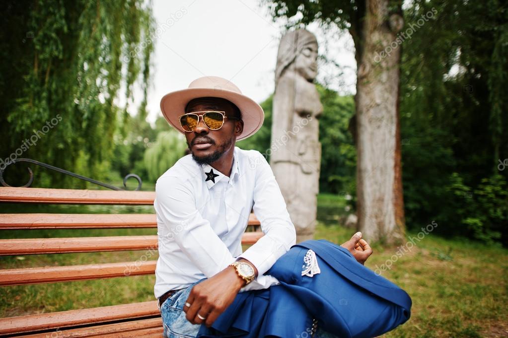 Багаті чорна людина сидить на лавці на Золотий сонцезахисні окуляри і  капелюхи — Фото від ASphoto777 fd6adb4592870