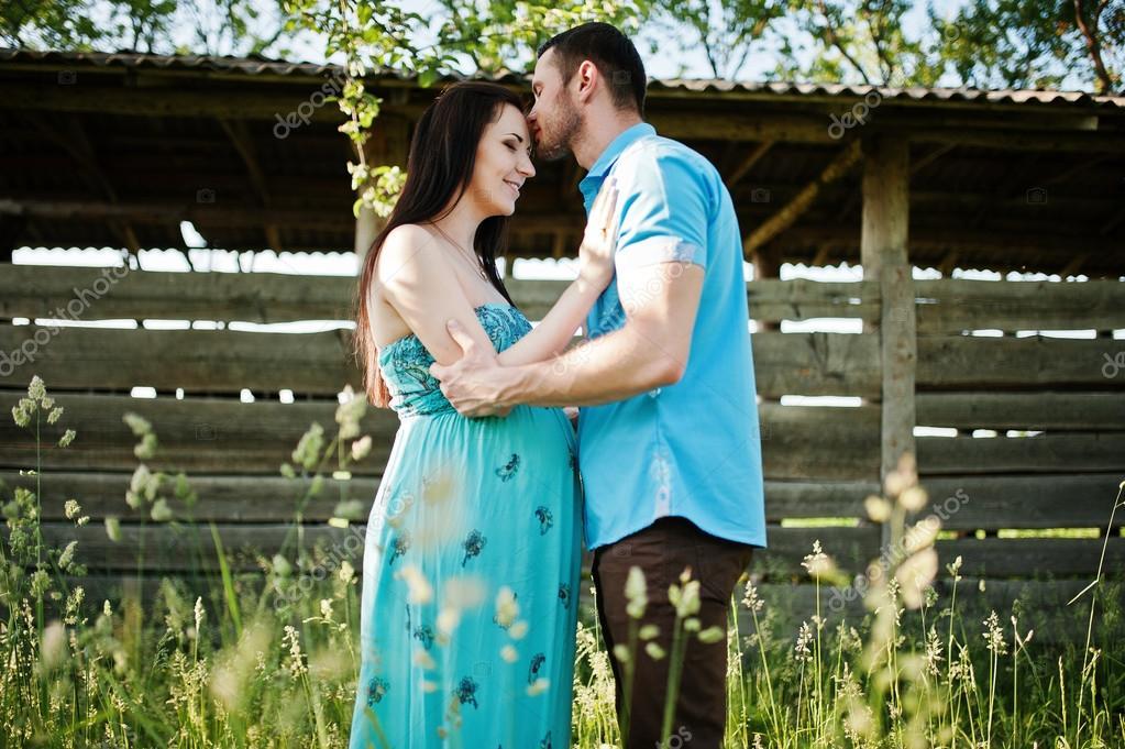 d3ecd503b8a Šťastný pár těhotná v tyrkysové šaty na zahradě — Stock Fotografie ...