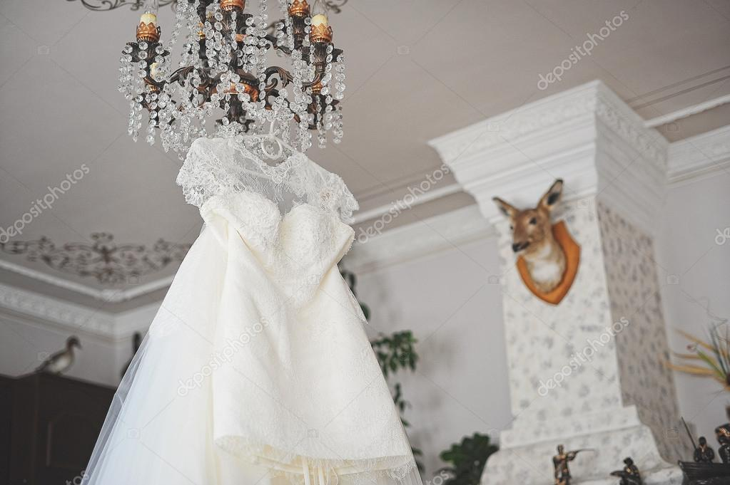 White Wedding Dress Hanging On The Chandelier Stock Photo 75754615