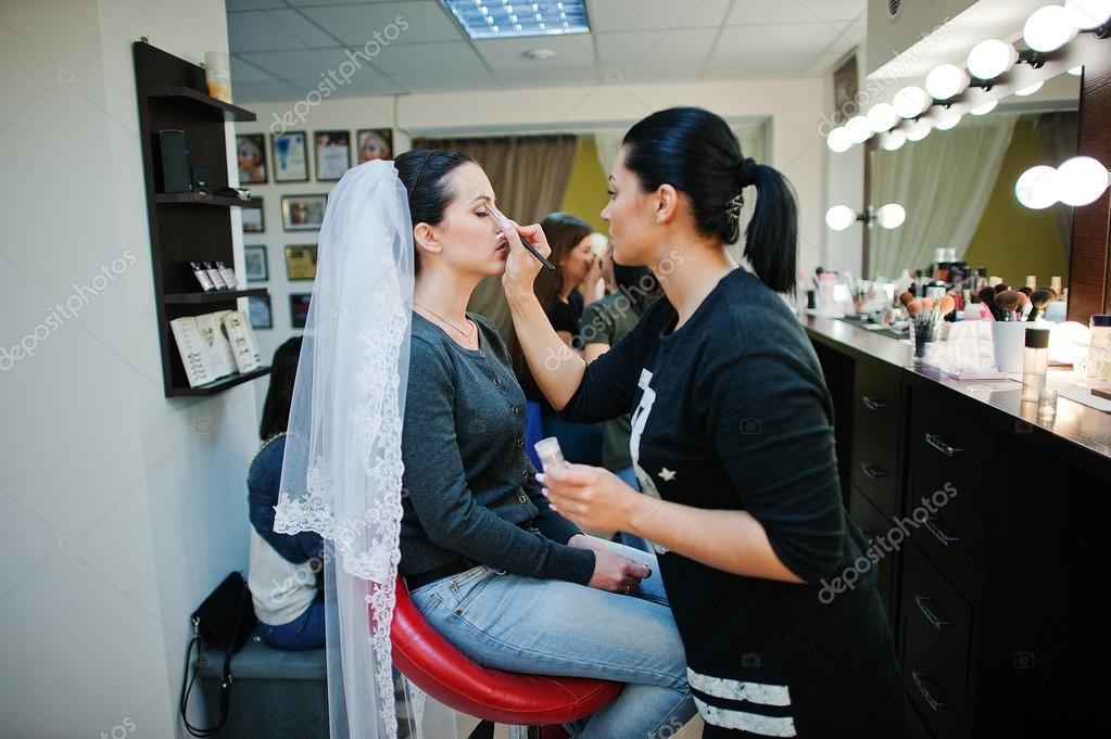 Make up artist doing make up for young beautiful brunette bride