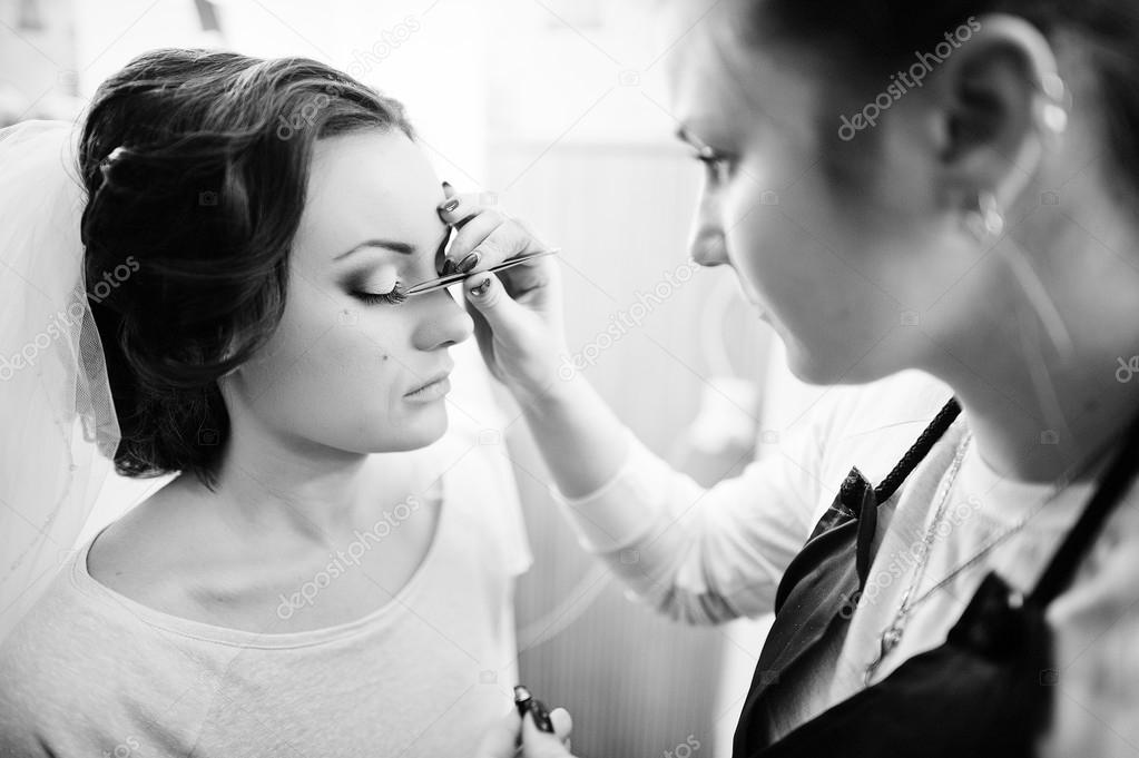 Beautiful young bride  sitting on chair and make up artist doing