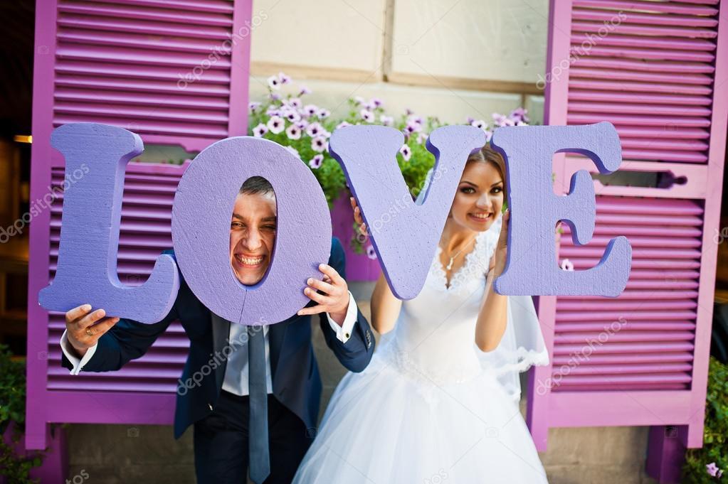 24682aa3df0b Sposi con decori viola parola amore sfondo viola legno wi — Foto Stock