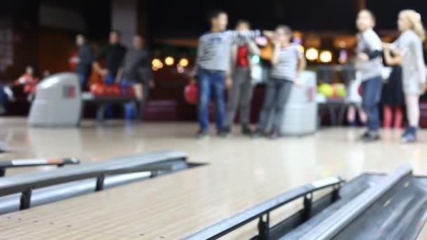 lidé hrát bowling, rozostřené pozadí