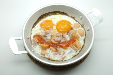 Fried egg with ham and sausage in a pan