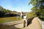 Fotografie Riverside mit Brücke über den Fluss Isar in München, Bayern Deutschland Europa