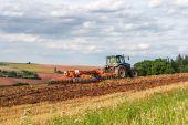 Farmář v traktoru, pracující na poli
