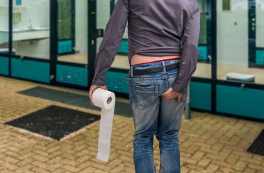 Man has diarrhea. Man holding toilet paper and his butt.