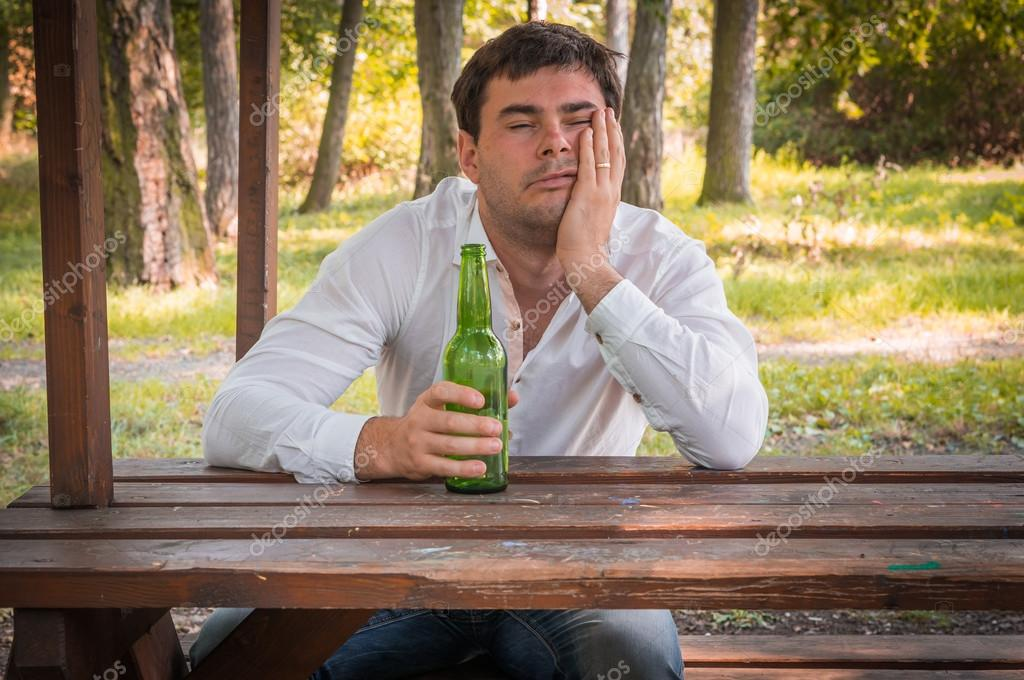 Drunk man sitting on a bench and holding a beer bottle