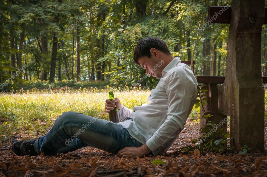 Drunk man lies on the ground near bench with a beer bottle