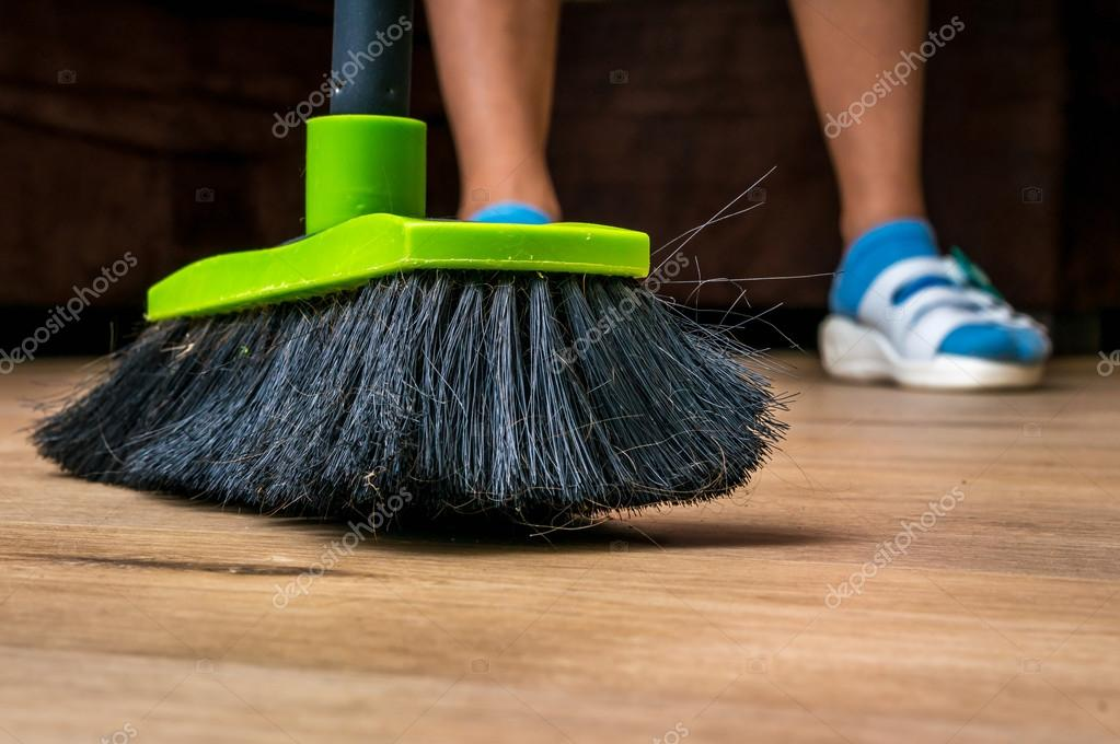 Woman With Broom Sweeping Wooden Laminate Floor Stock Photo