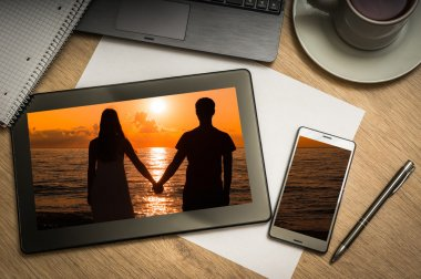 Digital tablet with silhouette of a loving couple on screen