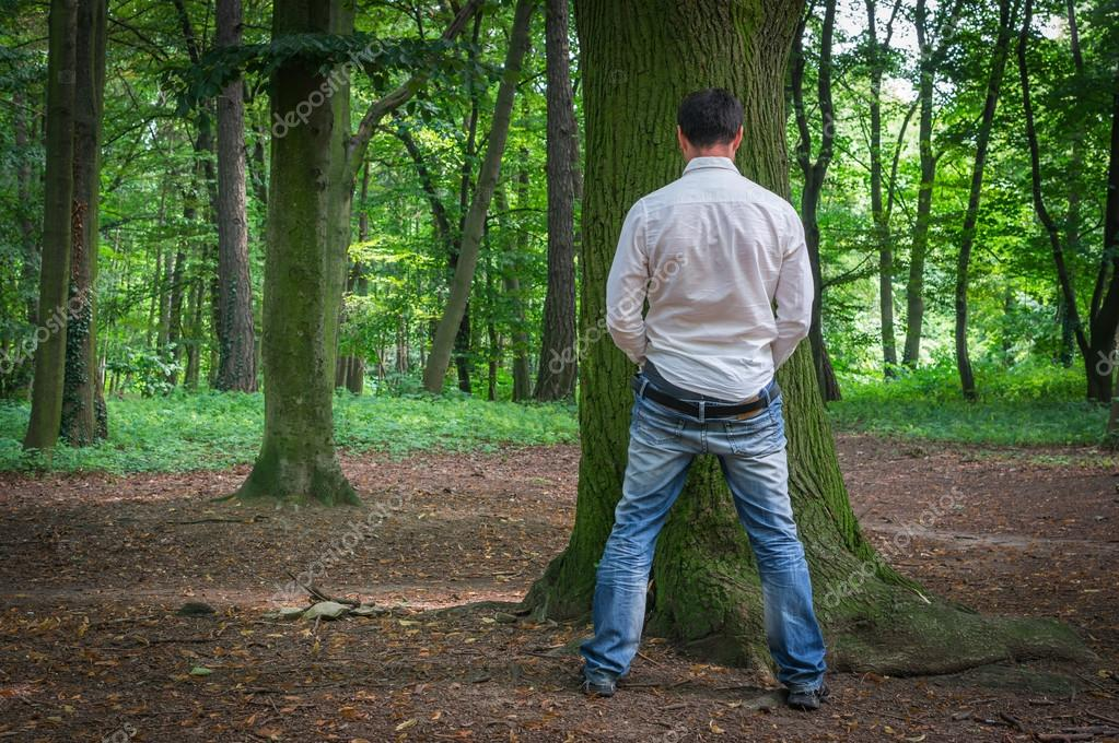 Standing man peeing near big tree in summer forest