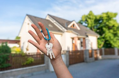 Real estate agent giving house key to a new property owner